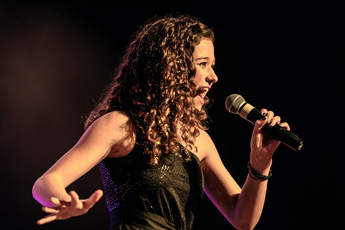 woman in blue singing