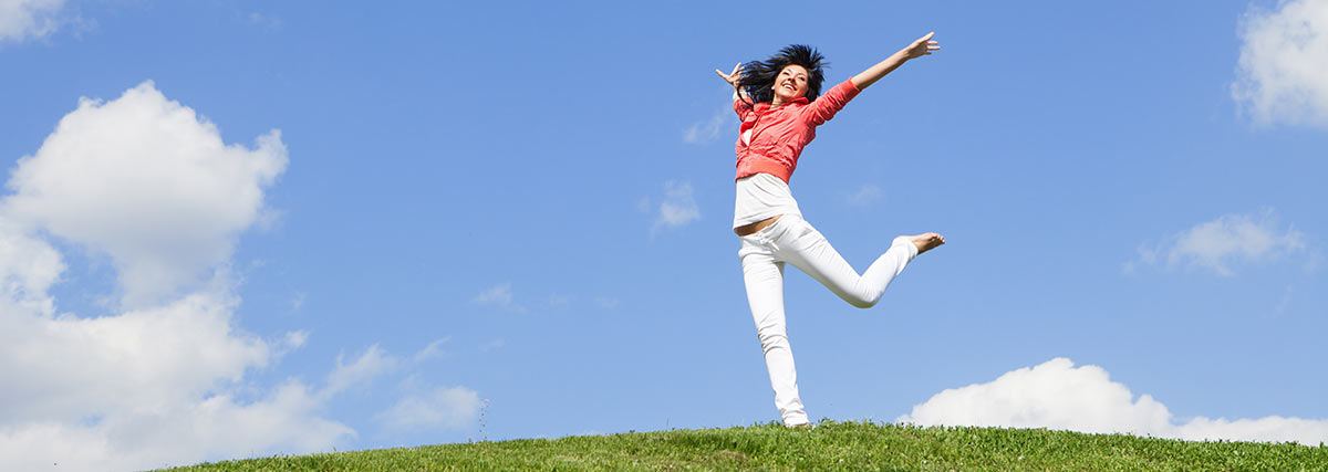 happy woman jumping on an open field