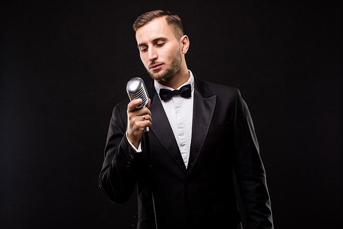 man in suit singing feat