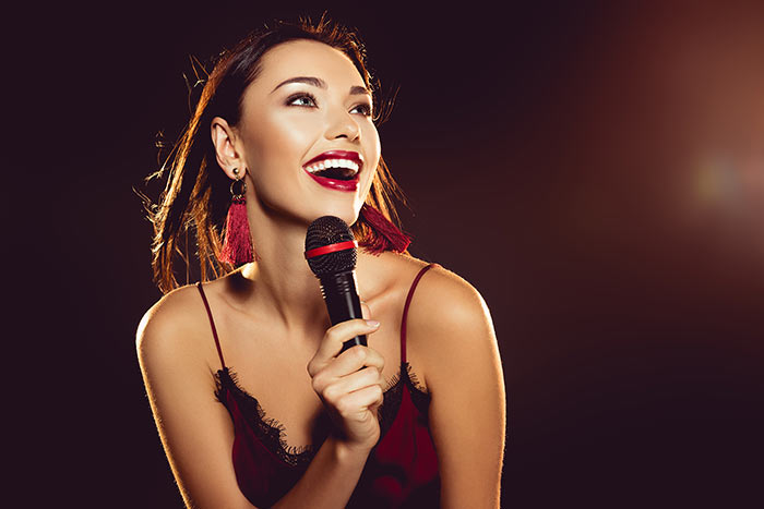 woman in red singing feat