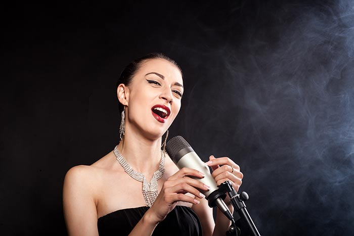 woman singing on a microphone feat