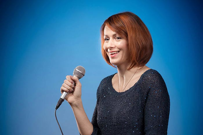 woman with blue background singing feat